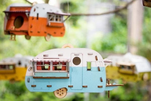 Four different camper bird houses hanging outside