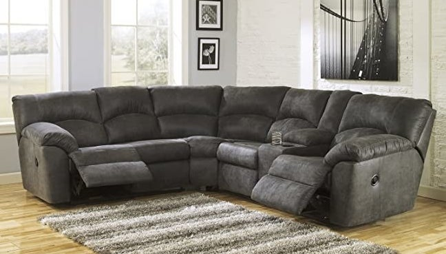 A dark gray L-shaped sectional with both the end seats in a reclining position and two cup holders by the right-most seat