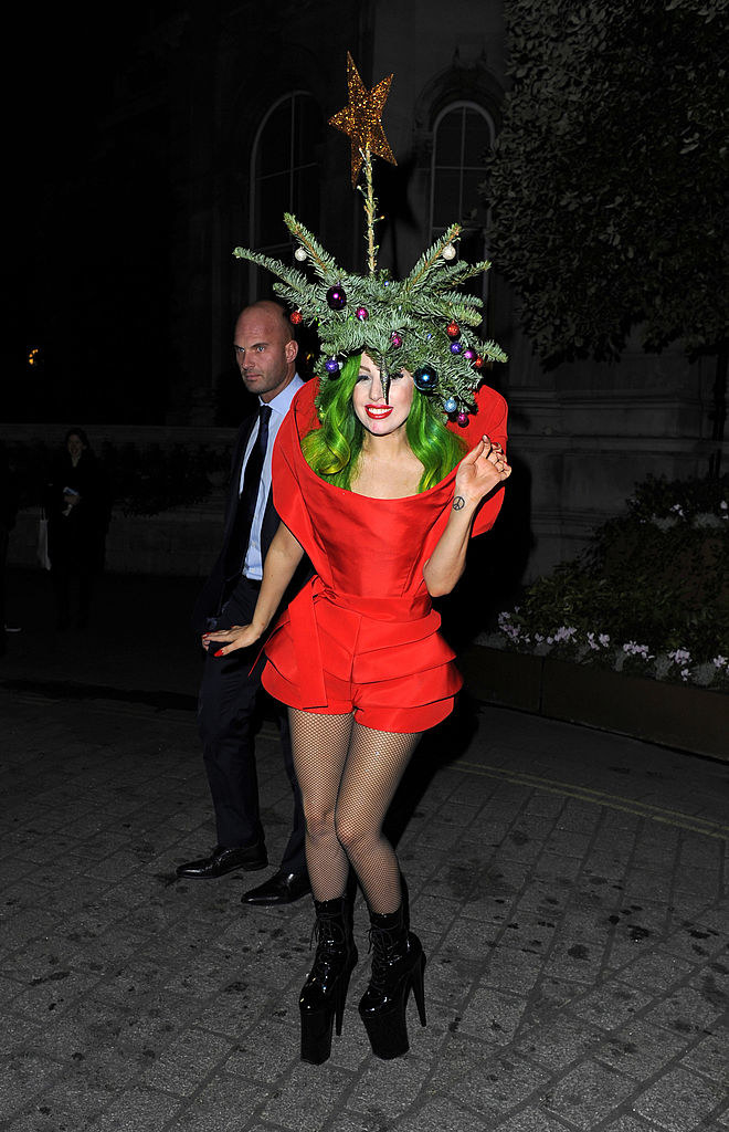 Lady Gaga wearing a red dress, green wig, and part of a Christmas tree, star topper included, on top of her head