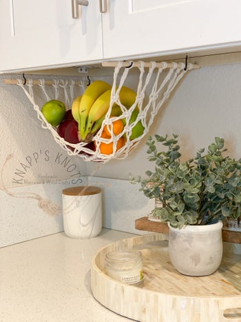 Fruit in the hammock hanging from some cabinets