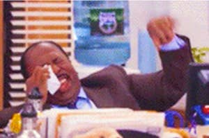 Stanley from the Office laughing and wiping his eye