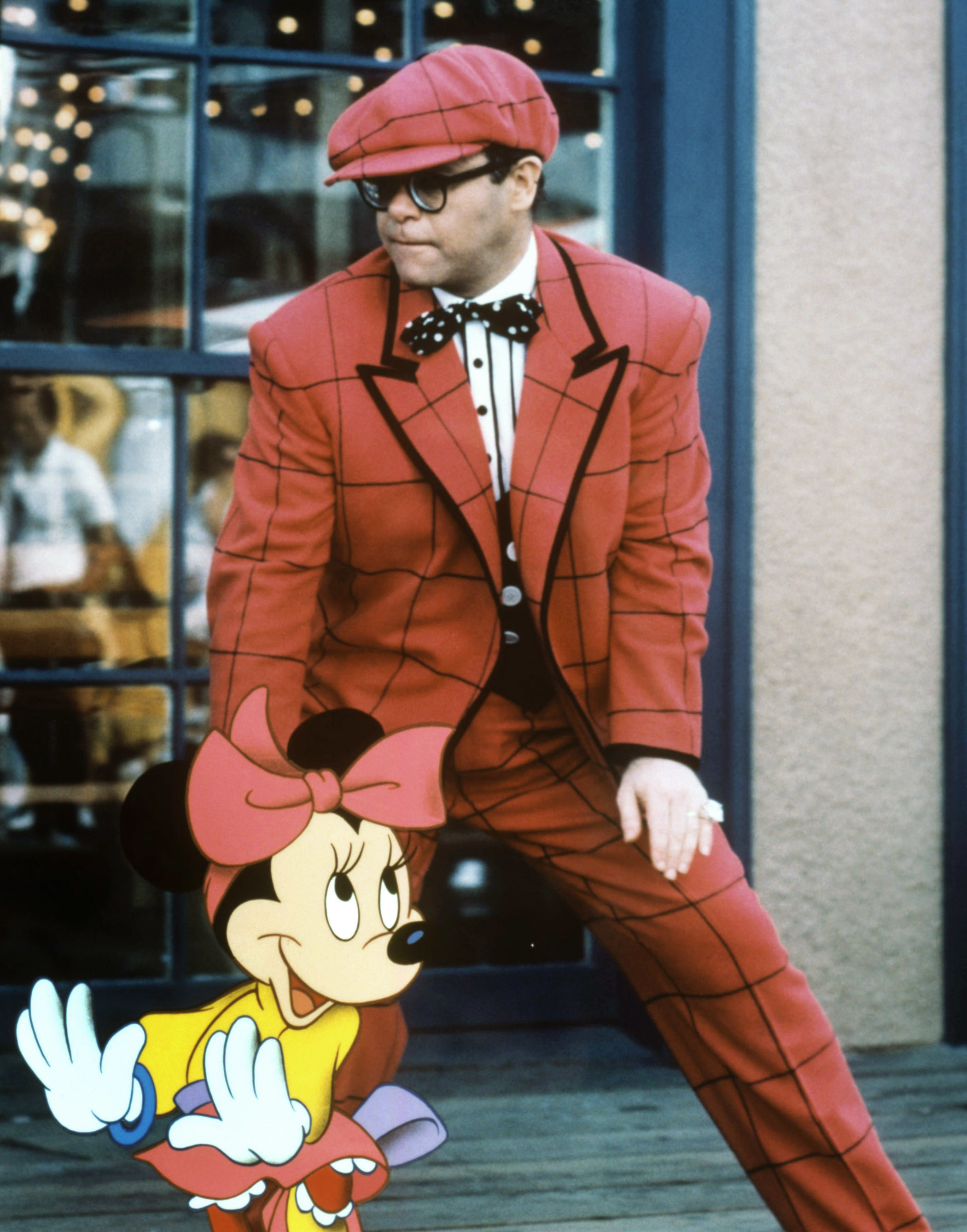 Minnie Mouse dancing with Elton John, who is in a dark pink plaid suit