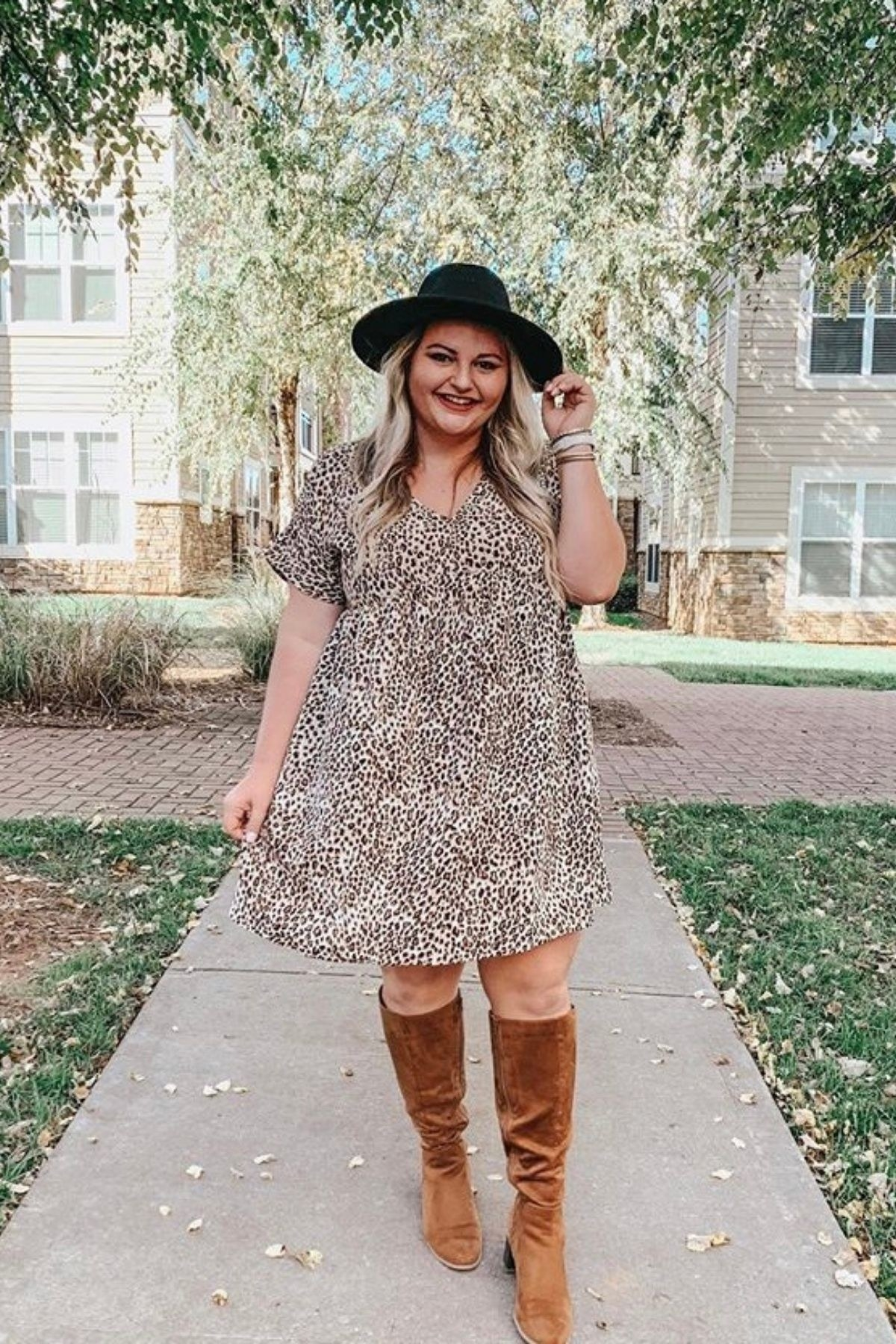 model in short-sleeve leopard-print babydoll dress and knee-high brown boots