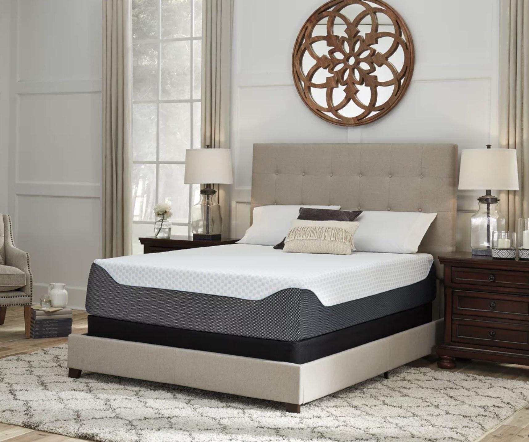 A white fabric frame and memory foam mattress