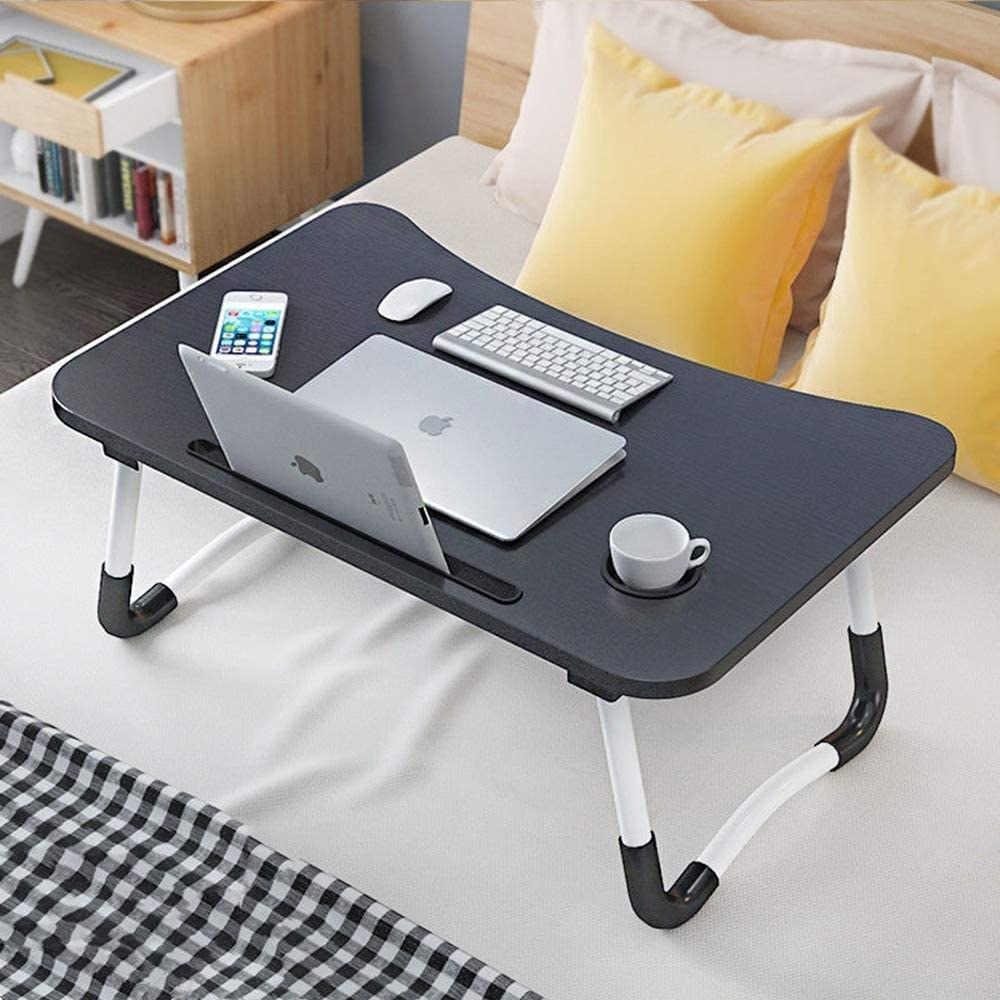 Lap desk placed upright on bed with laptop, coffee mug, iPad, mouse, keyboard, and iPhone on top