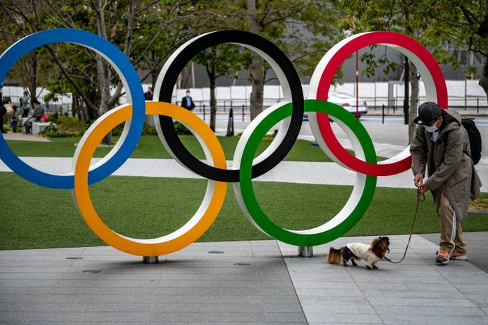 A man and his dog stands by a sculpture of the interlaced Olympic rings