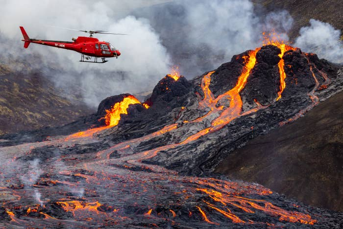 Helicopter flies over volcano with lava