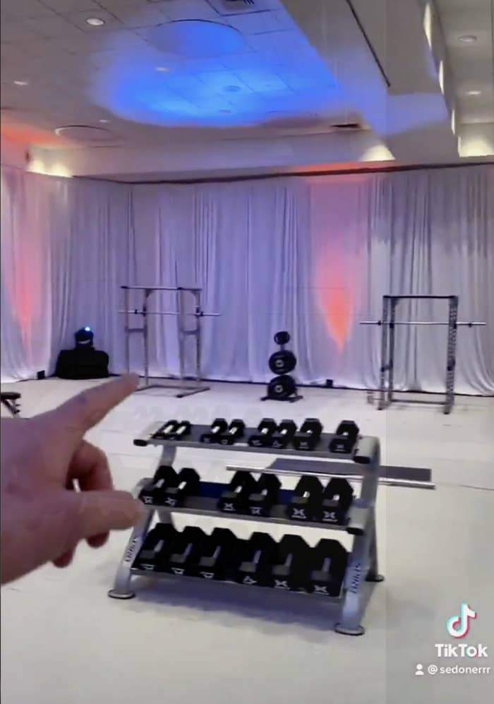 A large empty hall with a single dumbbell rack