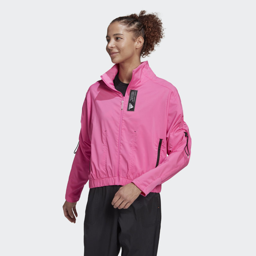 Model wearing pink zip up jacket with black side pocket zippers