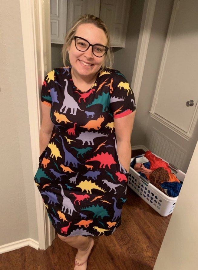 a reviewer wearing the black dress with a colorful dinosaur print on it