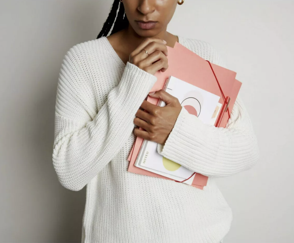 Model holding Noted by Post It folio