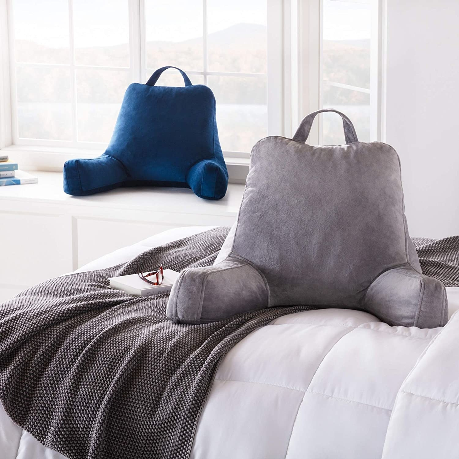 One gray sitting pillow placed on bed and one navy sitting pillow placed on window ledge