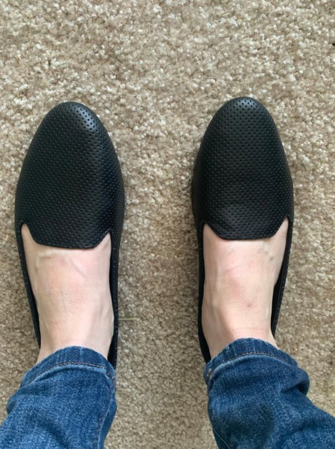 A reviewer wearing the perforated loafers in black