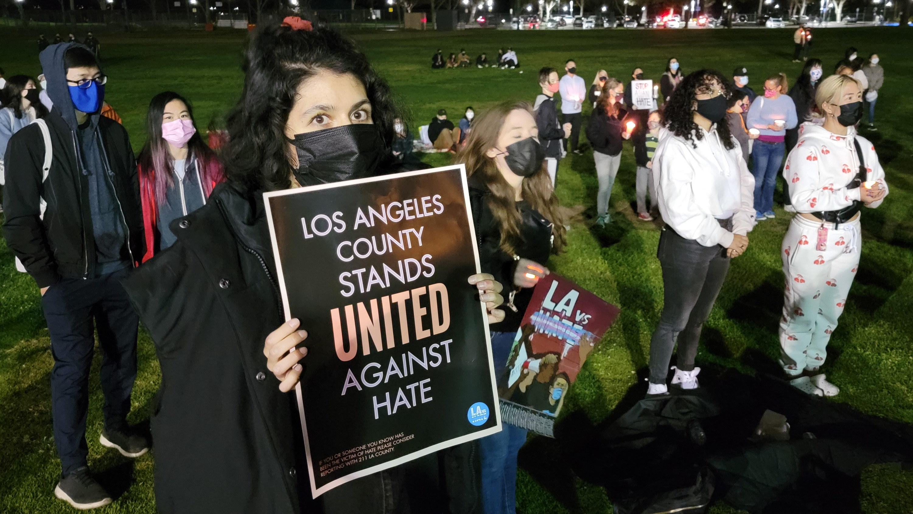 """Woman holds a sign reading, """"Los Angeles County stands united against hate"""""""