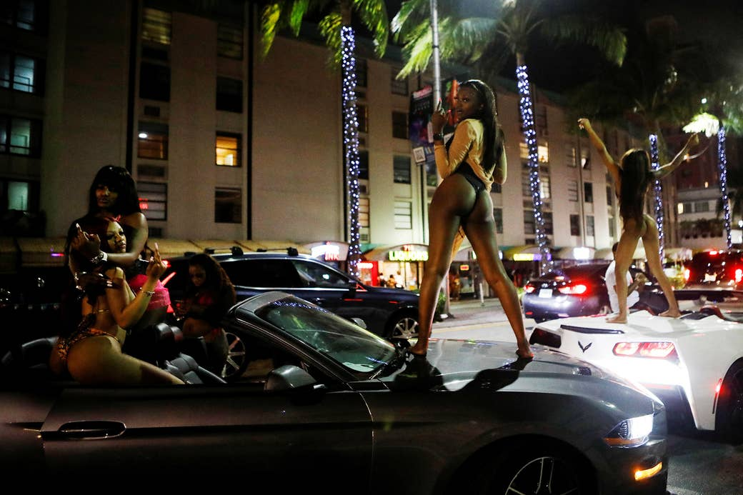Women wearing swimsuits pose on top of sports cars at night