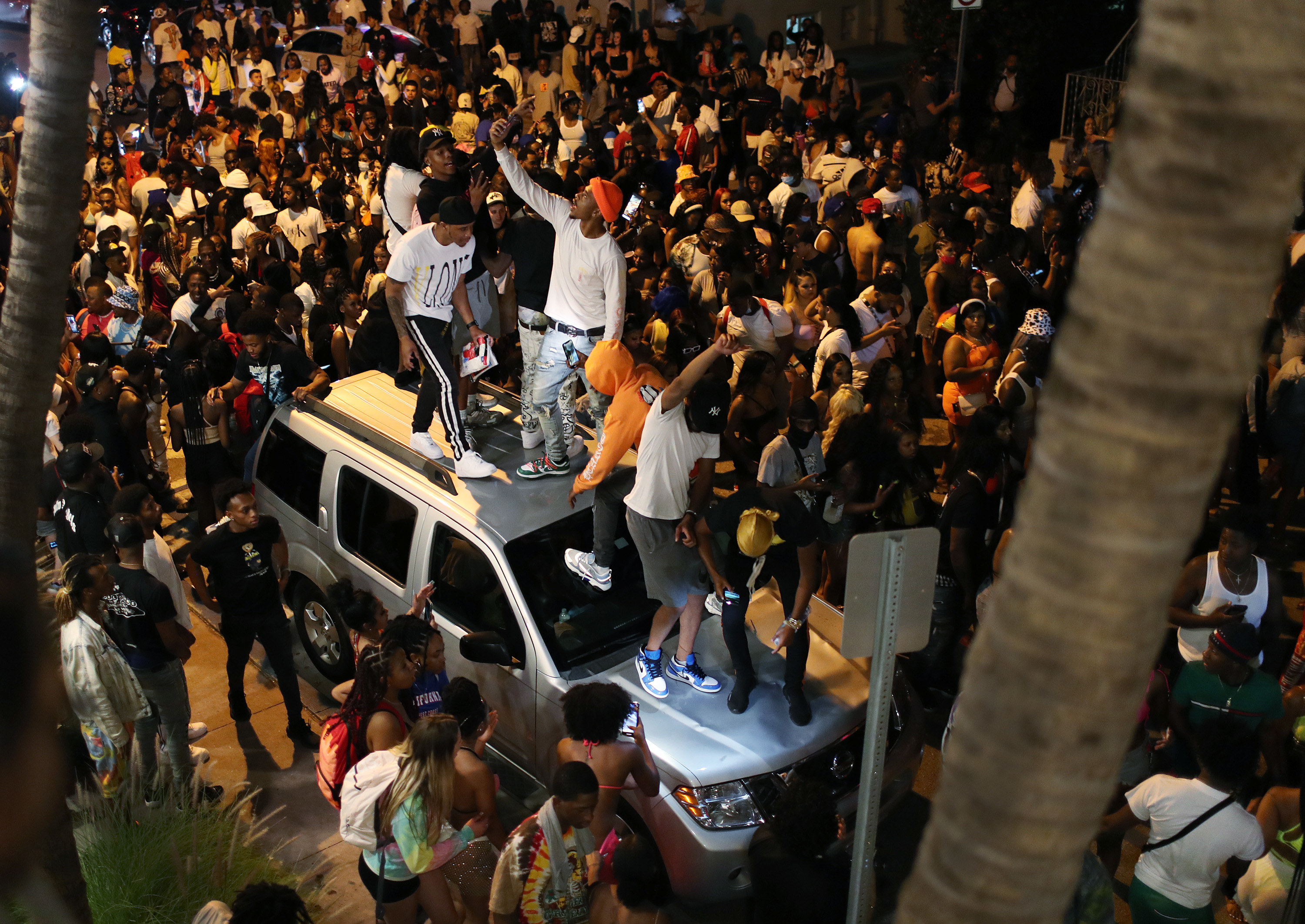 A group of guys on top of a car on a crowded street