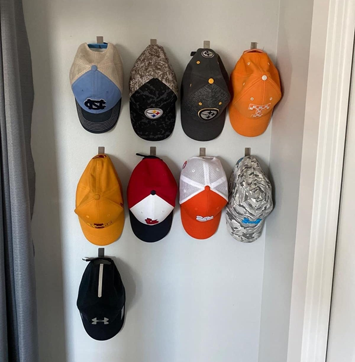 reviewer showing their nine baseball caps hanging neatly on the wall hooks