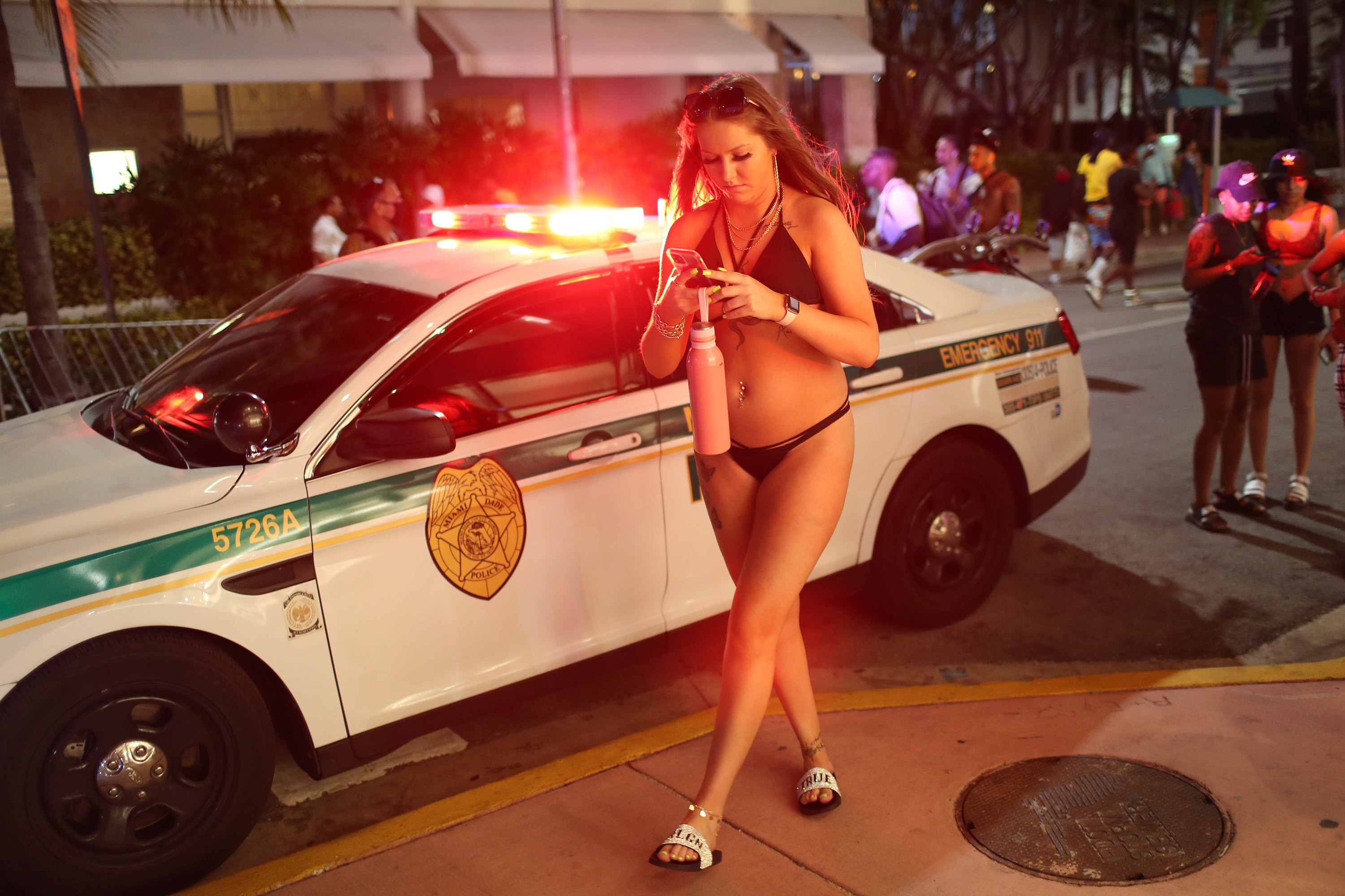 A woman in a bikini on her phone walks past a cop car