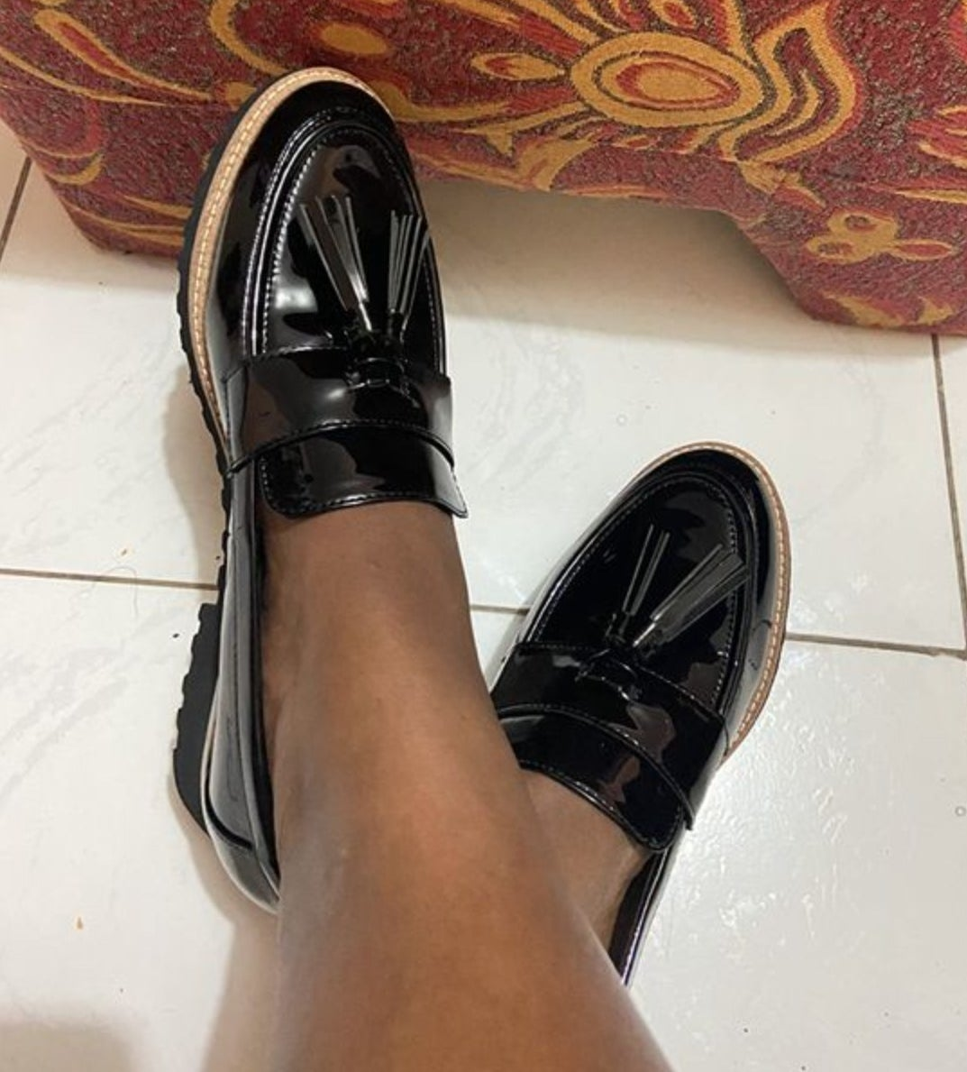 A reviewer wearing the chunky sole tassel loafers in black