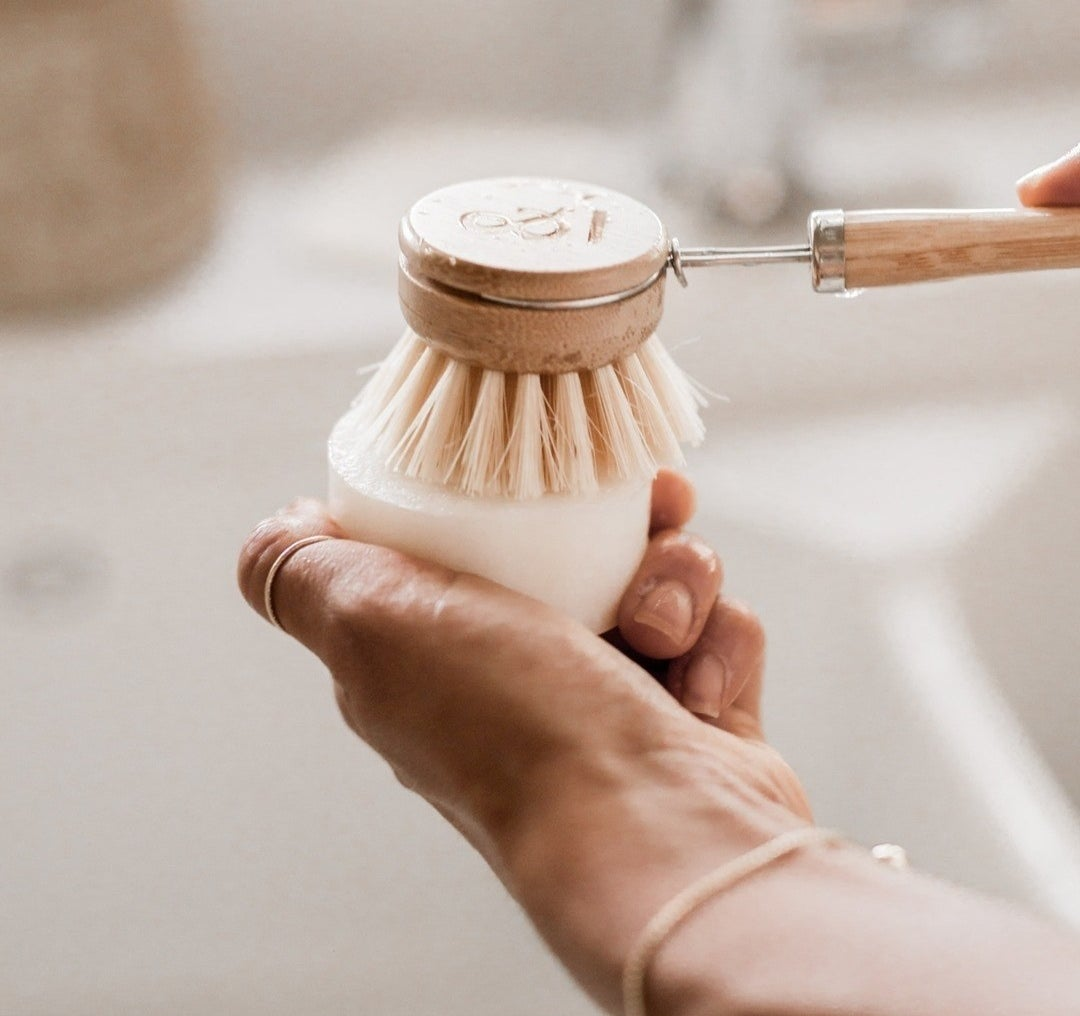 A person rubbing a dish brush on the solid washing bar