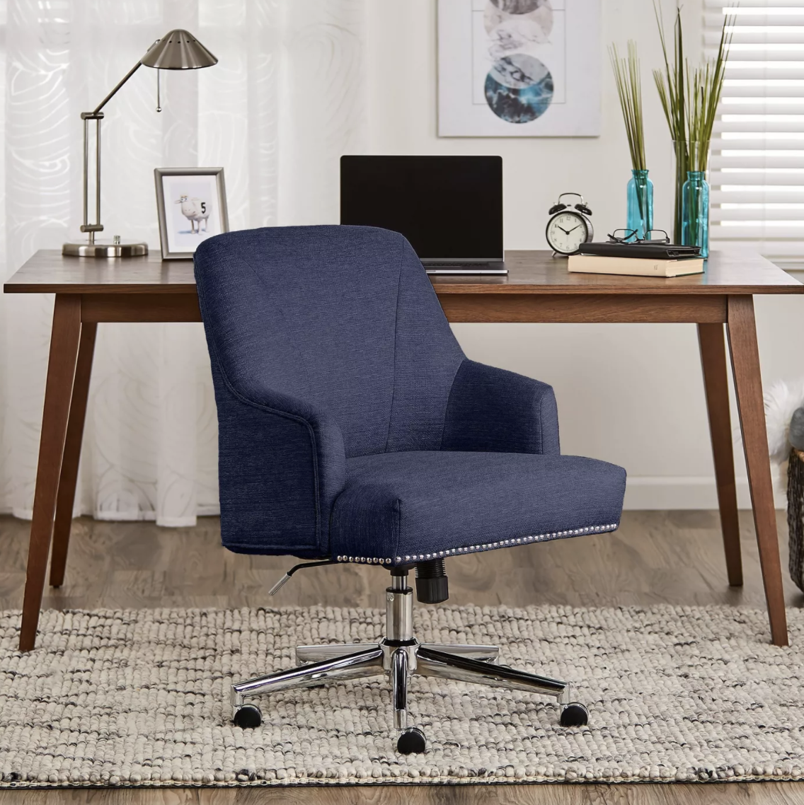 The navy office chair with studs around the rim of the chair in a home office