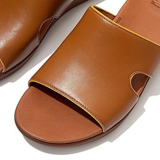 The sandal, which has a flat bottom and a thick strap with a small, semi-circular cut-out on either side of the mid-foot, in light tan