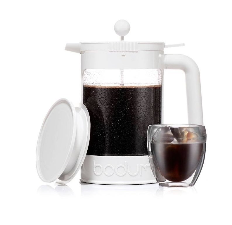white french press style cold brew maker filled with coffee and next to a glass of iced coffee