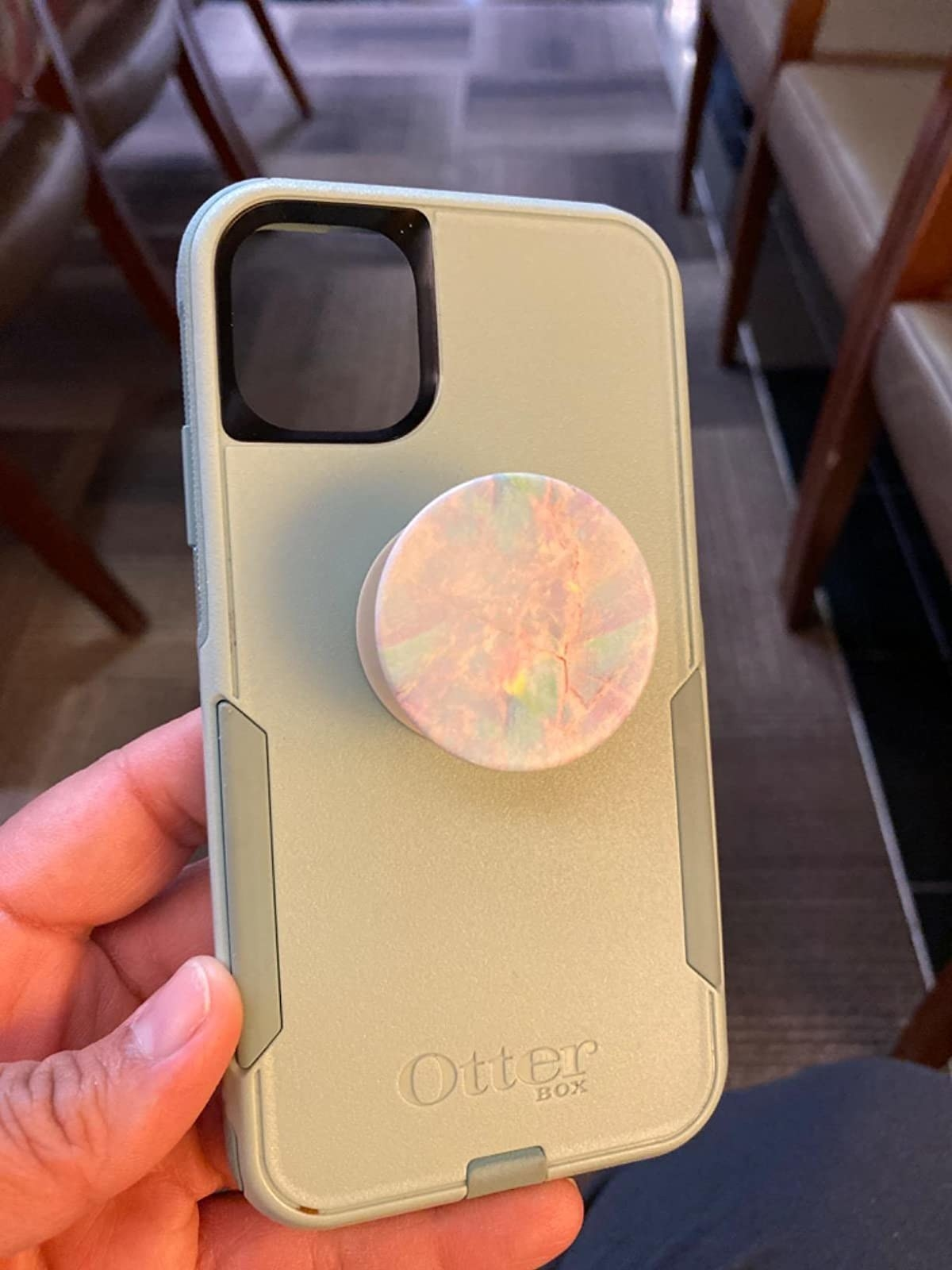 a reviewer holding a mint otterbox case with a marbled popsocket in the middle