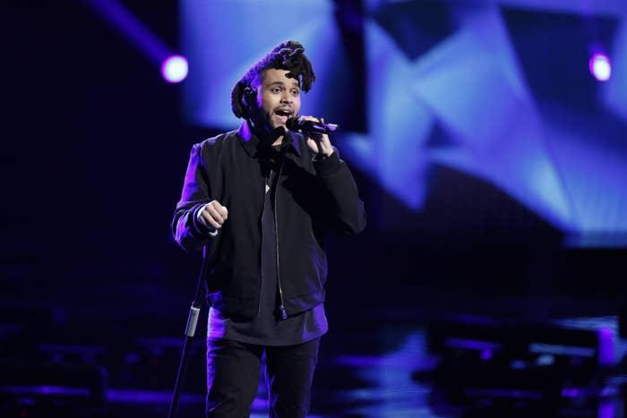 The Weeknd dressed in black and singing onstage