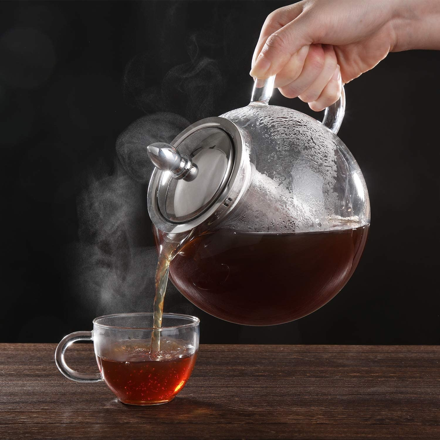 A person pouring tea from the pot into a glass teacup