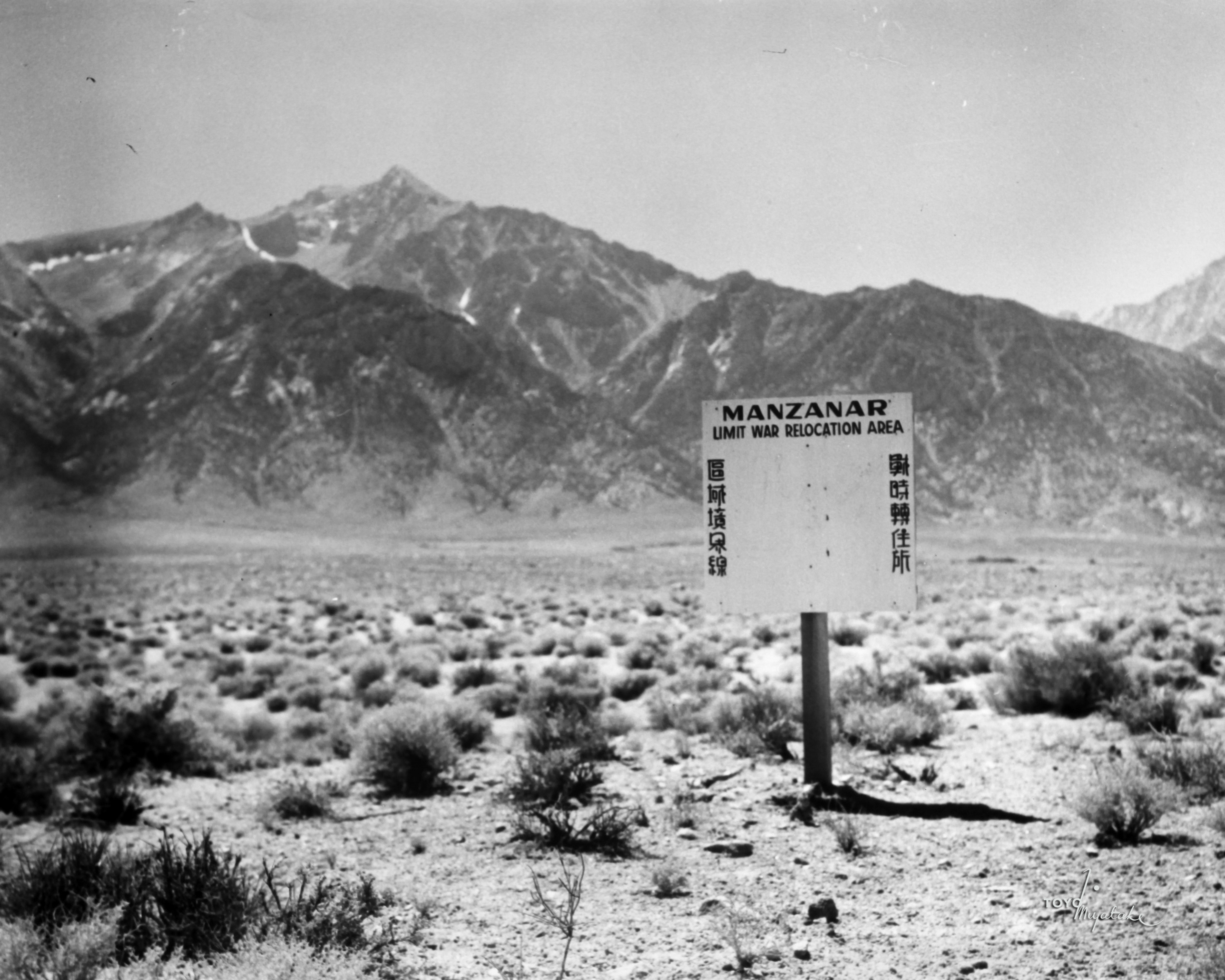 "Mountains in distance and a sign in a desert that reads ""Manzanar Unit War Relocation Area"""