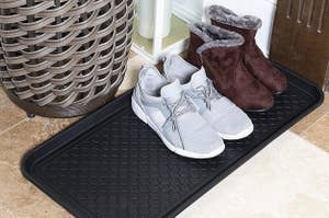 black textured boot tray with sneakers and boots on it
