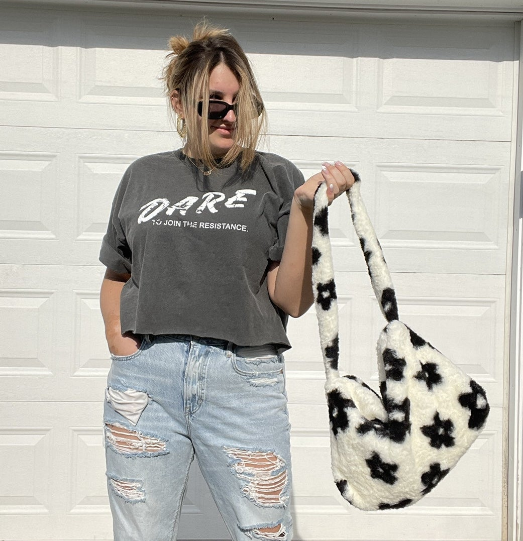 buzzfeed writer holding a white fuzzy purse printed with black flowers
