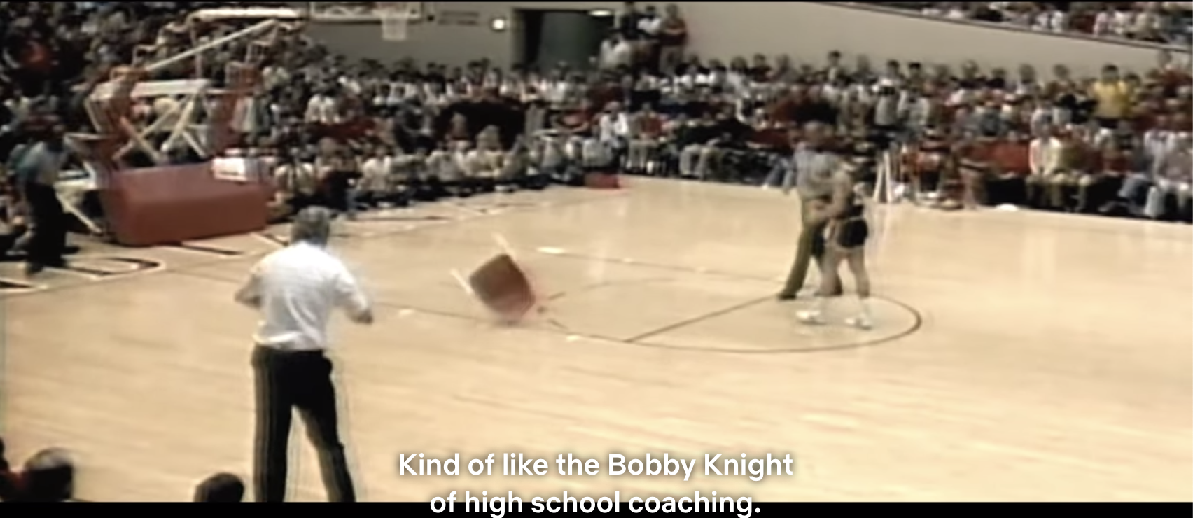Singer throwing a chair in the middle of the court during a basketball game