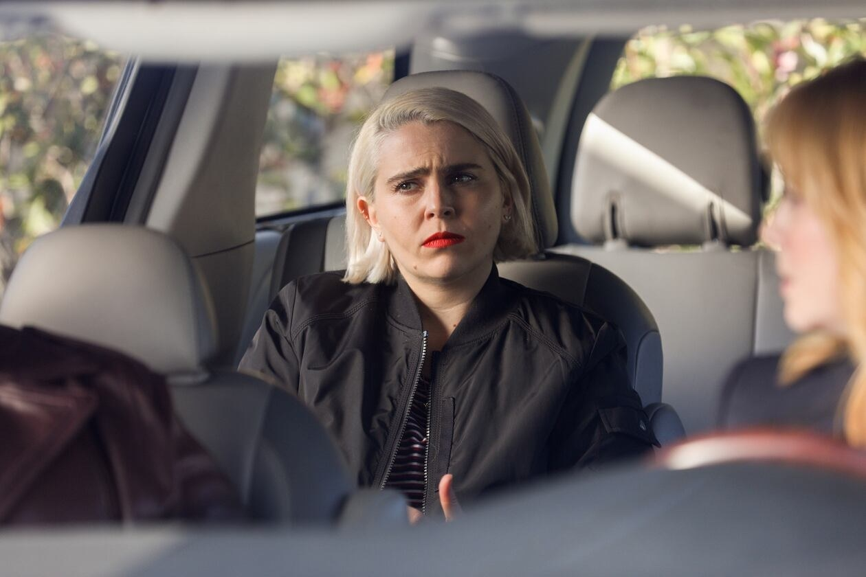 Annie with red lips and blonde hair, frowning in the back seat of a car