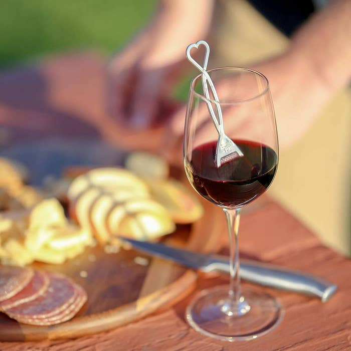 a Wand Wine Purifier in a glass of red wine that sits on a wooden table