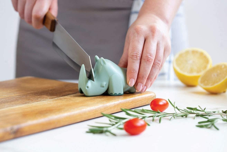 a model sharpens a knife on the green rhino blade sharpener