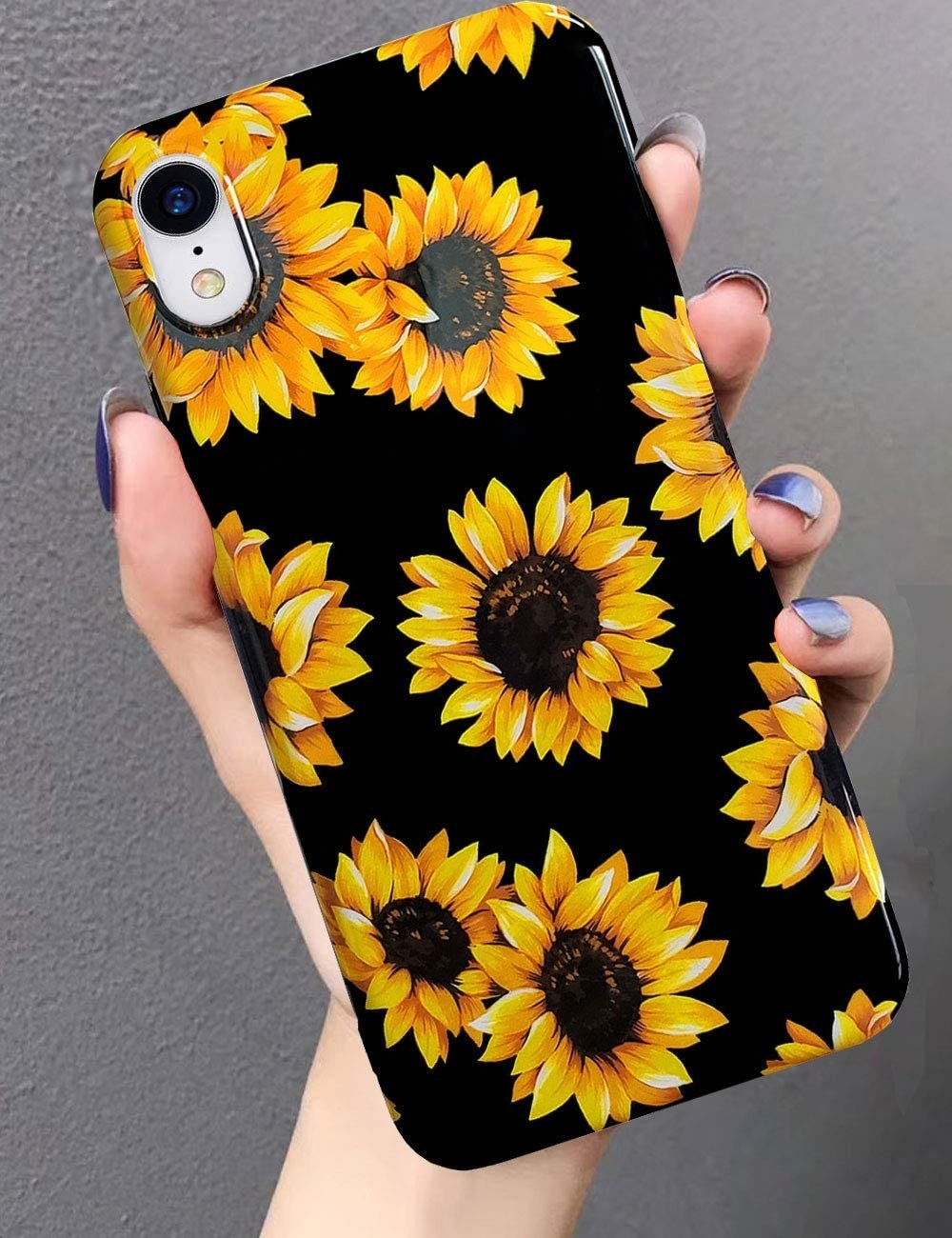 a model holding a black phone case with sunflowers on it
