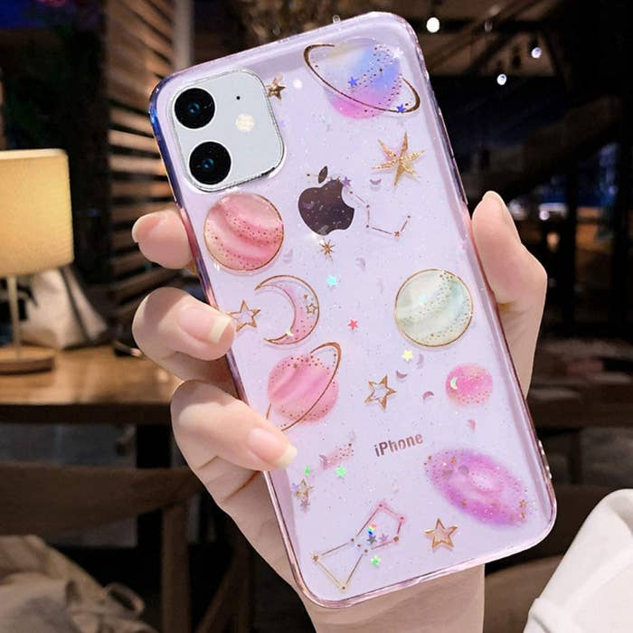 a model holding a translucent pink iphone case with various planets moons and stars on it