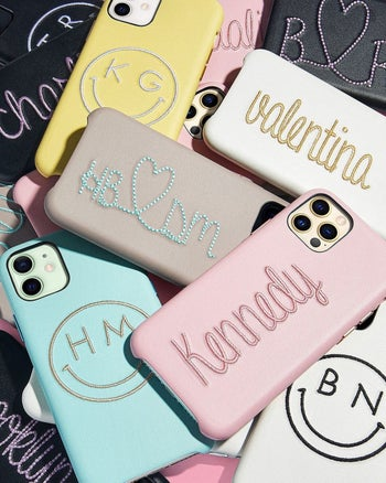 a pile of different colored phone cases with various things embroidered on them