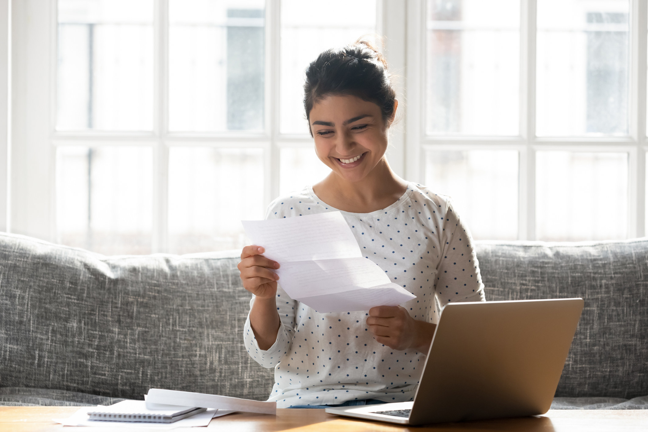 A woman smiling down at a college admissions letter