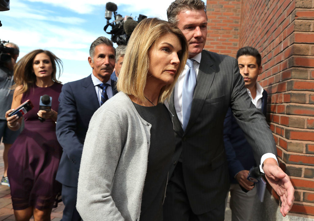 Lori Loughlin and her husband Mossimo Giannulli, behind her at left, leave the John Joseph Moakley United States Courthouse in Boston