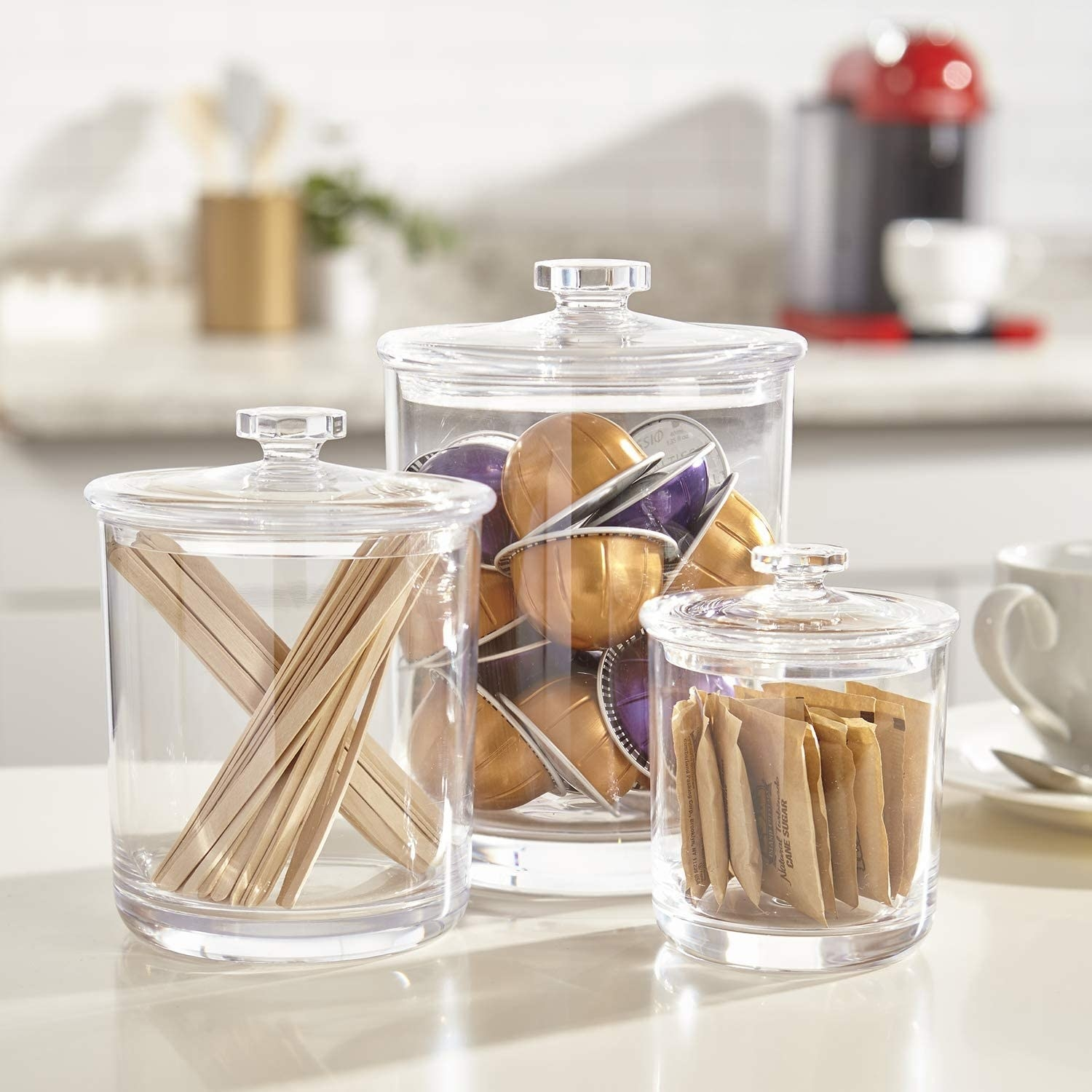 the three containers on a counter filled with nespresso pods, sugar packets and stir sticks
