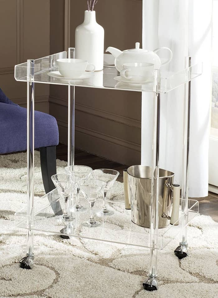 the cart with tea accessories on the top and martini glasses and an ice container on the bottom