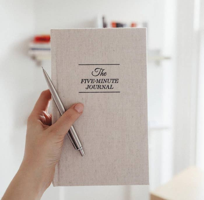A person holding the journal and a pen