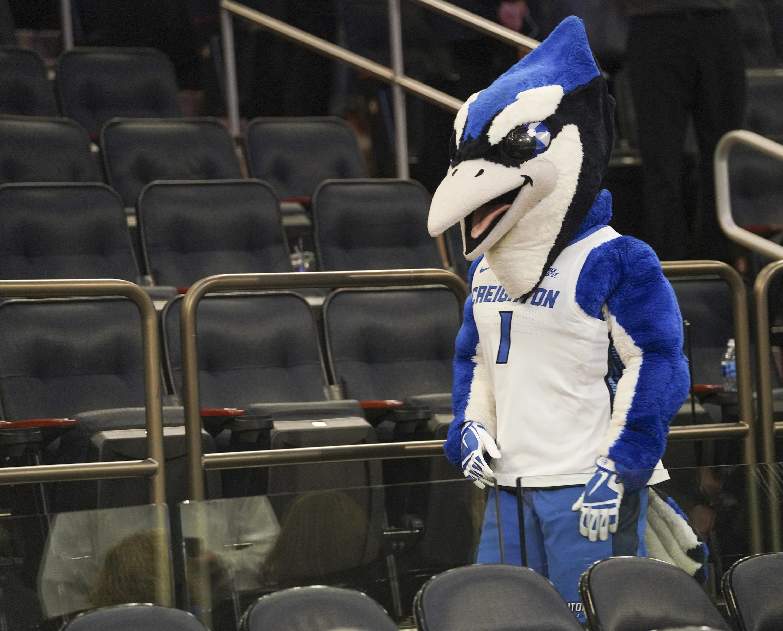 Blue jay mascot near empty seats.
