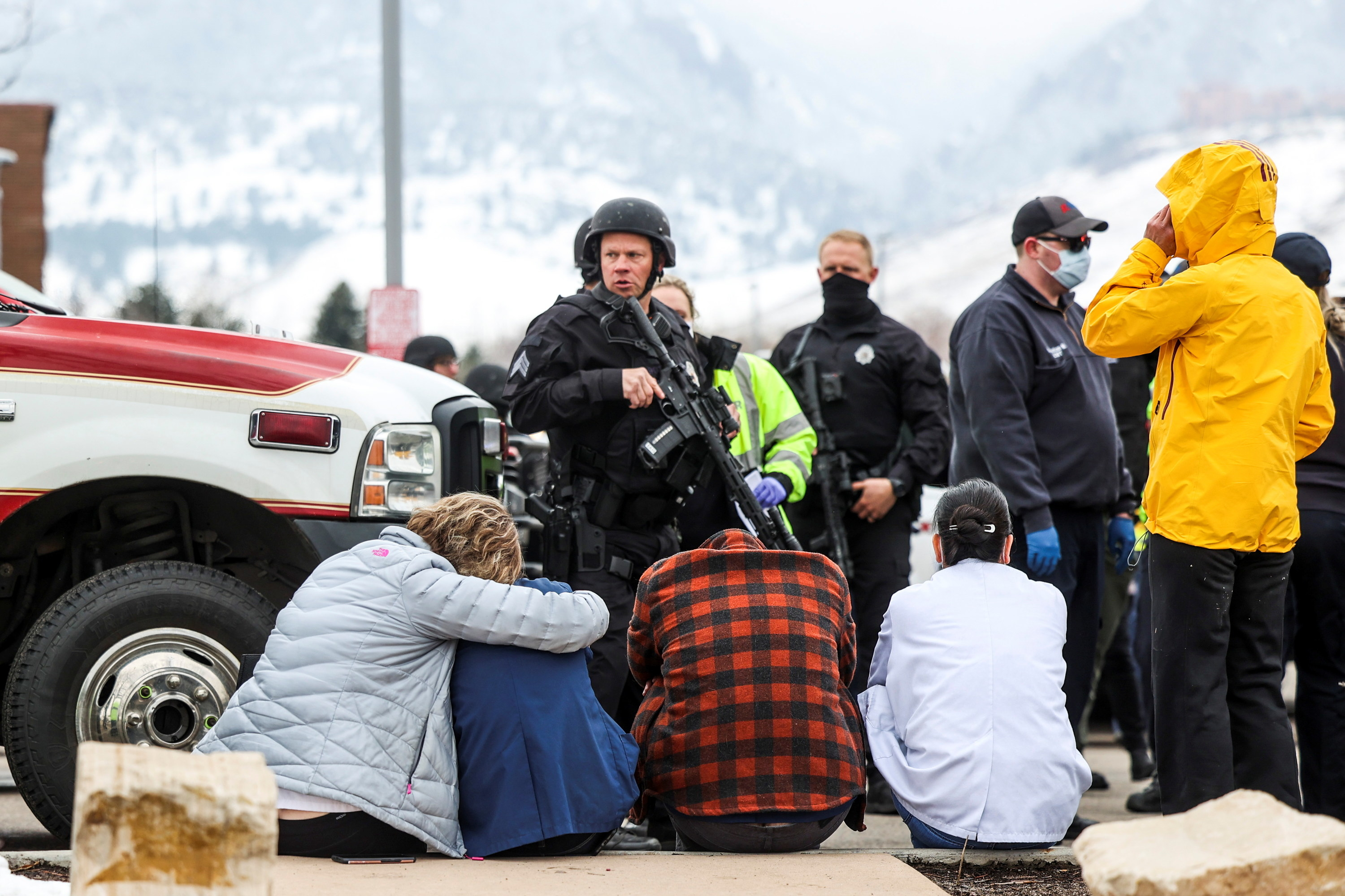 Armed police stand in the parking lot while people sit huddle on the curb