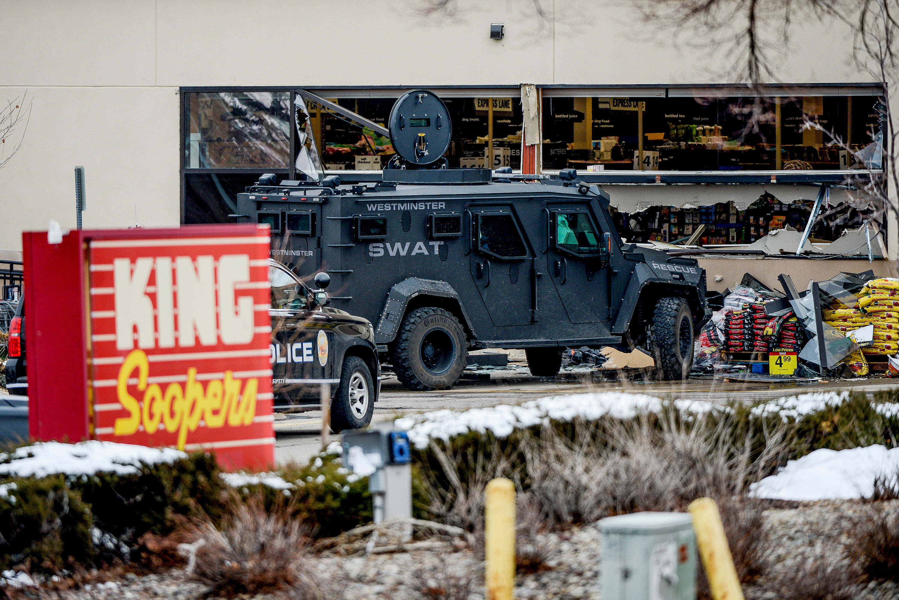 A SWAT vehicle and a police car in the parking lot of King Soopers