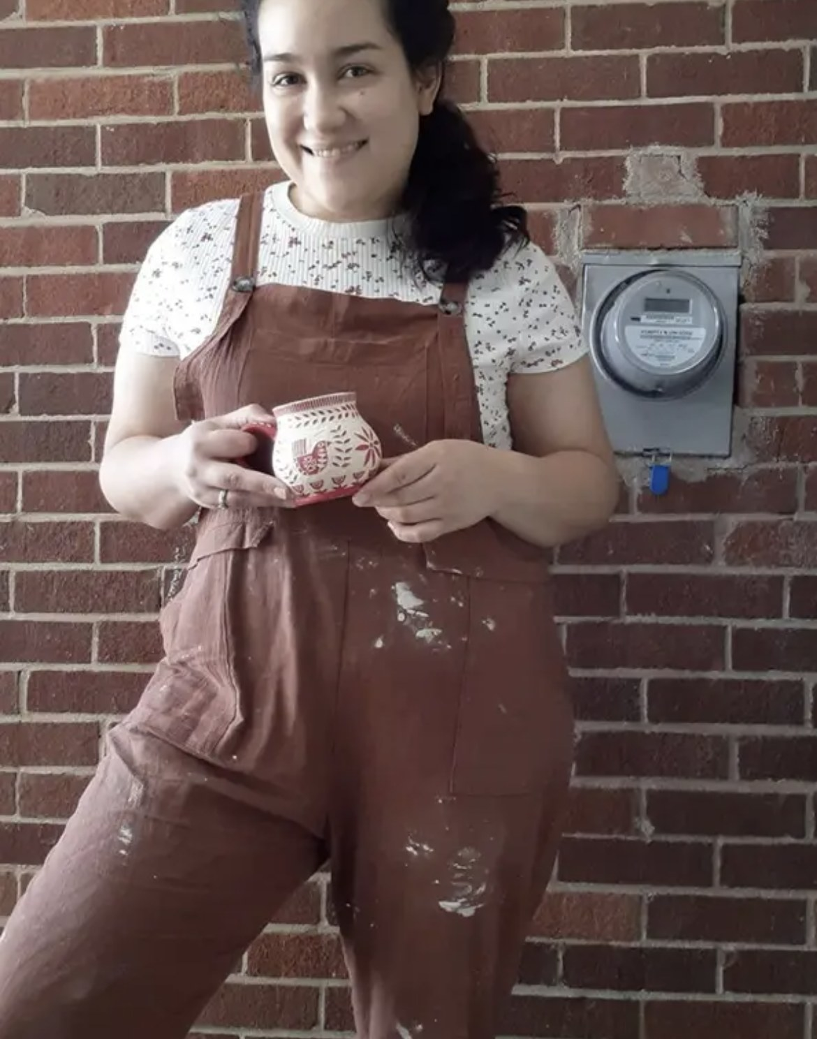 Person is wearing a pair of mauve overalls and a white top
