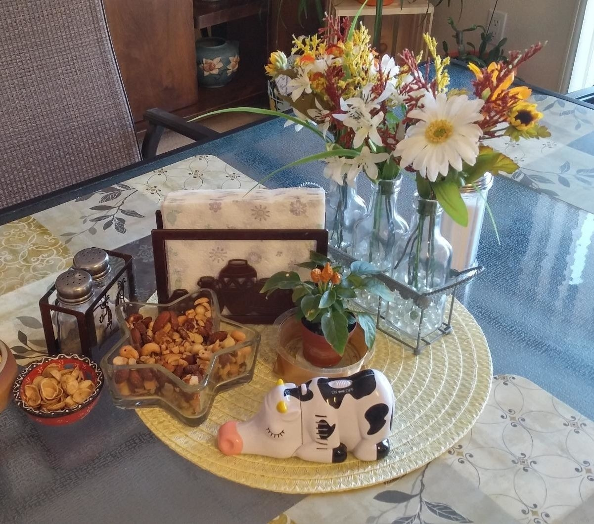 reviewer image of the wrapables cow mini tabletop vacuum in the center of a dining table along with bowls of snacks, napkins, and a salt and pepper shaker